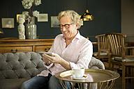 Smiling senior man in lounge room using phablet - TOYF001274