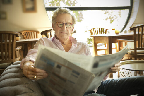 Smiling senior man in lounge room reading newspaper - TOYF001276