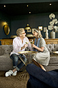 Smiling senior couple sitting on couch in lounge room clinking wine glasses - TOYF001382