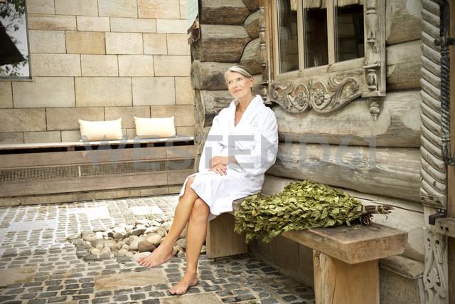 Smiling senior woman in bathrobe sitting outside Finnish sauna log cabin - TOYF001297 - Tomas Rodriguez/Westend61