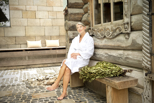 Smiling senior woman in bathrobe sitting outside Finnish sauna log cabin - TOYF001297