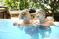 Happy senior couple in swimming pool at a spa - TOYF001312