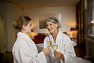 Smiling senior woman and adult daughter in bathrobes clinking champagne glasses - TOYF001318