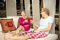 Happy senior couple sitting on lounge outdoors clinking cocktail glasses - TOYF001324