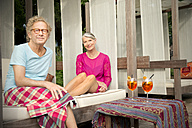 Smiling senior couple sitting on lounge outdoors with cocktails - TOYF001328