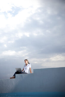 Spain, Mallorca, woman with laptop sitting on stairs besides in front of clouded sky - TOYF001181