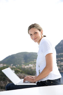 Spain, Mallorca, portrait of smiling woman with laptop - TOYF001184
