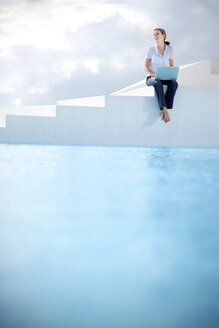 Spain, Mallorca, woman with laptop sitting on stairs with swimming pool in the foreground - TOYF001187