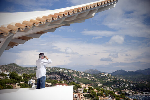 Spain, Mallorca, man standing on terrace of a house looking at view with binocular - TOYF001411
