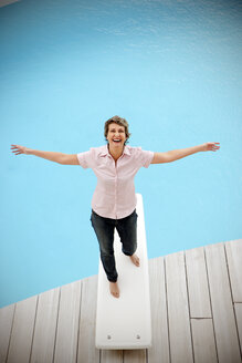 Portrait of happy woman standing on springboard with arms outstretched - TOYF001200