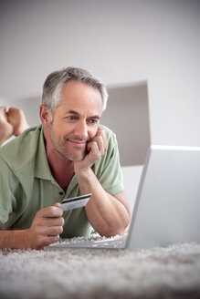 Portrait of smiling man lying with laptop on a carpet holding credit card - TOYF001201