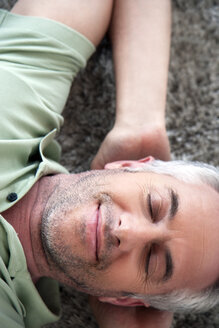 Portrait of smiling man with closed eyes relaxing on a carpet at home - TOYF001204