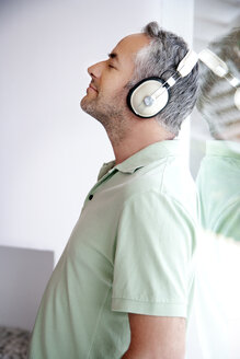 Portrait of man with closed eyes hearing music with headphones - TOYF001207