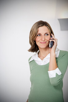 Portrait of smiling woman telephoning in the kitchen - TOYF001211