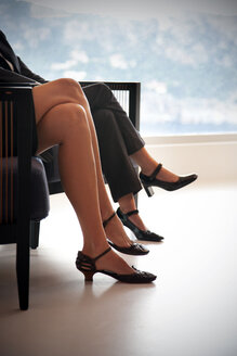 Legs of two businesswomen sitting siede by side on two armchairs - TOYF001222