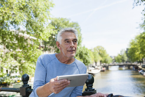 Netherlands, Amsterdam, senior man with digital tablet at town canal - FMKF002209
