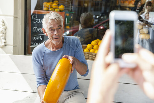 Netherlands, Amsterdam, cell phone picture of senior man sitting on bench holding loaf of cheese - FMKF002001