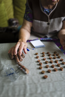 Elderly woman counting money, making stacks of Euro cents - RAEF000412