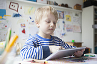 Portrait of blond little boy using digital tablet - RBF002993
