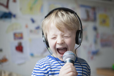 Portrait of singing little boy with headphones and microphone - RBF002990