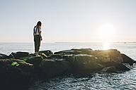 France, Pornichet, woman standing on rocks at seafront by sunset - GEMF000322