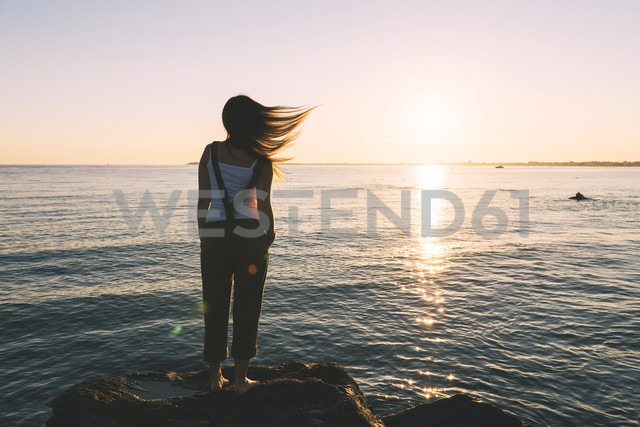 France, Pornichet, woman with blowing hair standing at seafront watching sunset - GEMF000321