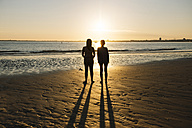 France, Pornichet, silhouettes of two women standing on the beach at sunset - GEM000336