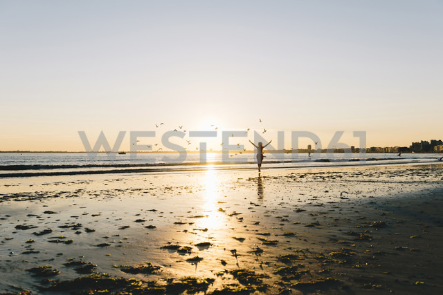 France, Pornichet, silhouette of running woman on the beach at sunset - GEMF000335