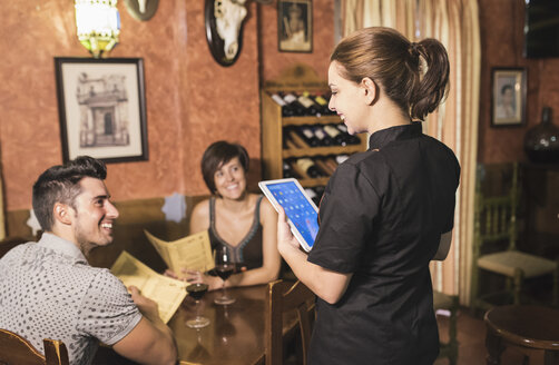 Waitress taking the order of couple in restaurant with digital tablet - JASF000027