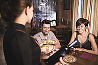 Waitress serving plate with salad to couple in restaurant - JASF000029