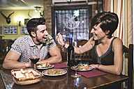 Couple in restaurant eating salad and playing with food - JASF000030