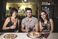 Portrait of three smiling friends in a restaurant - JASF000037