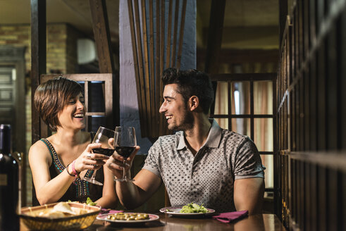Couple smiling and drinking wine in restaurant - JASF000042
