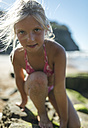 Portrait of little girl climbing on a rock at the beach - MGOF000595