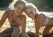 Portrait of two sisters head to head on the beach - MGOF000606