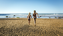 Back view of two sisters running  on the beach - MGOF000608