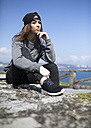 Spain, Gijon, portrait of young woman wearing baseball cap sitting on a wall - MGOF000618