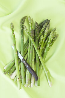 Green asparagus and kitchen knife on green cloth - ASF005677