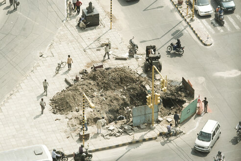 India, Dehli, Construction site in street with construction workers and pedestrians - MFR000378