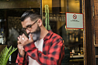 Hipster lighting a cigarette in front of a bar with smoking ban - JASF000055