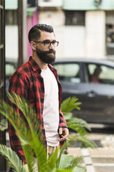 Hipster with cigarette standing in front of a bar - JASF000057