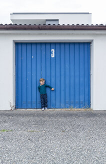 3 year old boy in front of garage door with number 3 - OPF000079