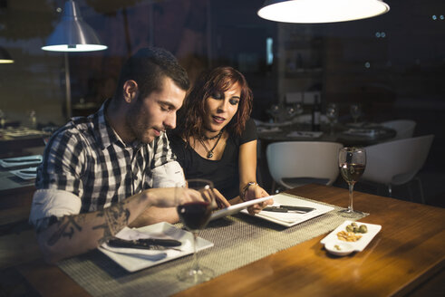 Young couple with digital tablet in a restaurant at night - JASF000067