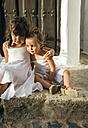 Spain, Balearic Islands, Menorca, Binibeca, portrait of two little sisters sitting on steps side by side - MGOF000650