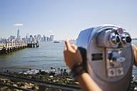 USA, New York City, view to the skyline with person using coin operated binoculars in the foreground - GIOF000104