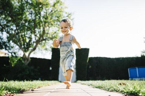 Little boy running barefoot on floor plates in the garden - JRFF000040