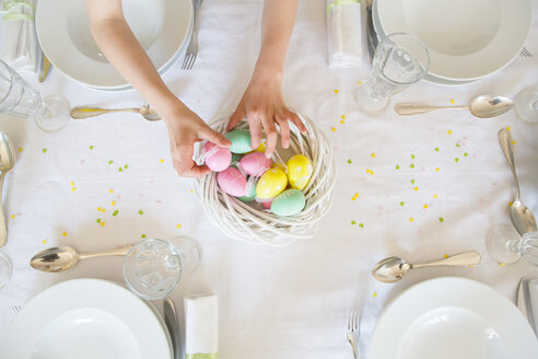 Little girl decorating dining table with Easter eggs - LVF003782