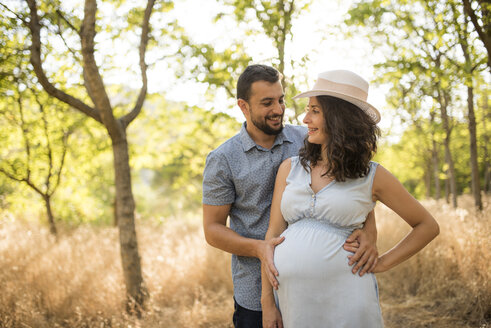 Happy pregnant woman and her partner relaxing in nature - JASF000076