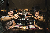 Happy couple in a bar toasting red wine glasses - JASF000089