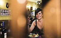 Smiling woman holding red wine glass in a traditional Spanish bar - JASF000093